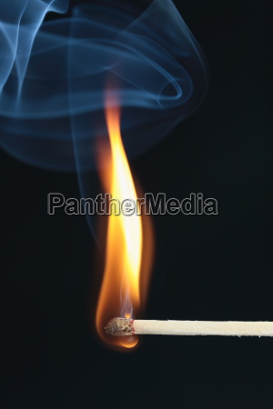 inflamed match with blue smoke on