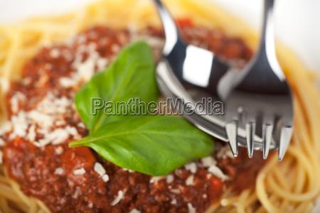 teller mit spaghetti bolognese und basilikumblatt
