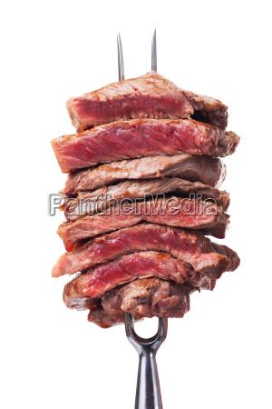 slices steak on a meat fork