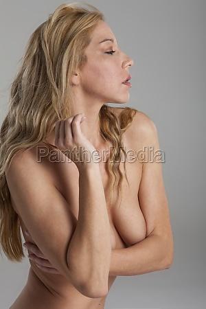 blonde nackte frau auf grauem hintergrund