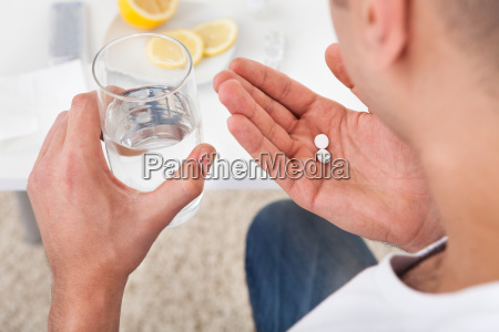 homem doente que toma comprimidos com