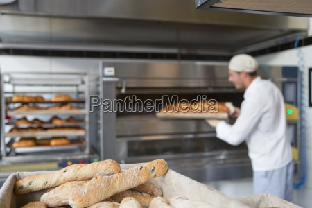 baker holding tray of bread in