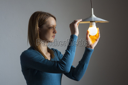 young, woman, with, a, light, bulb - 14696971