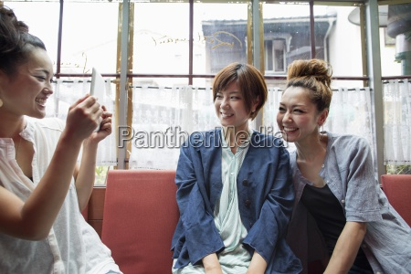 three women sitting indoors one holding