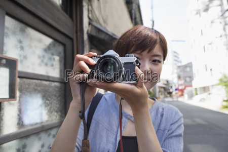 woman standing outdoors looking through a