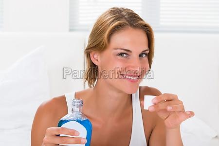 woman holding bottle of mouthwash