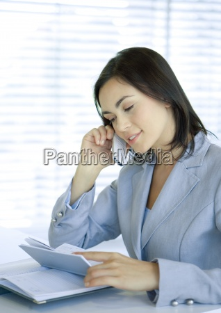 businesswoman using cell phone and looking