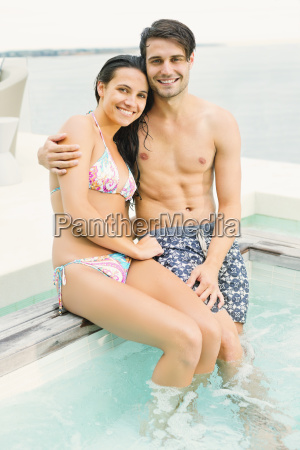 couple relaxing at edge of swimming