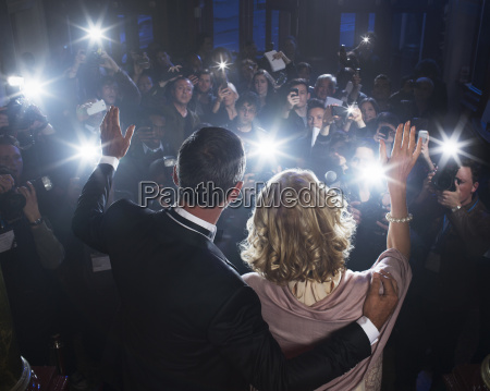 celebrity couple waving to paparazzi at