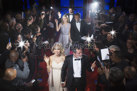 well dressed celebrities waving to paparazzi