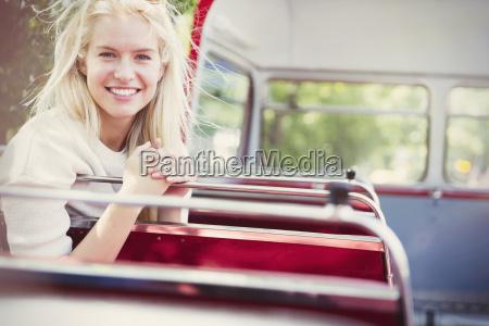 portrait smiling woman riding double decker