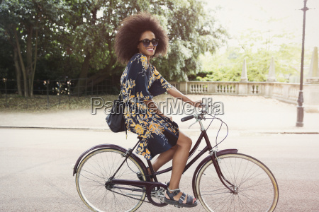 portrait smiling woman with afro riding