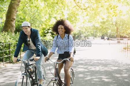 friends riding bicycles in park