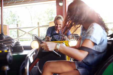 young couple riding bumper cars at