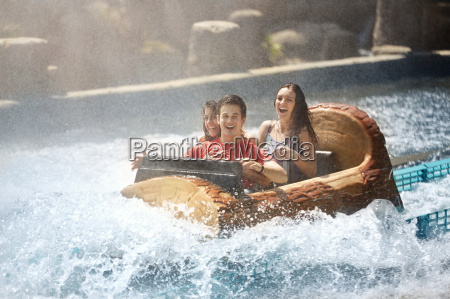 wet friends laughing on water log