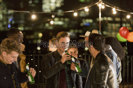 young men drinking beer at rooftop