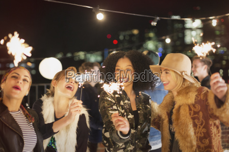 young women with sparklers at rooftop
