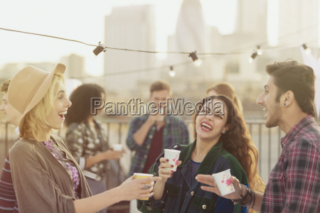 young adult friends laughing and drinking