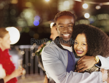 portrait smiling young couple hugging at