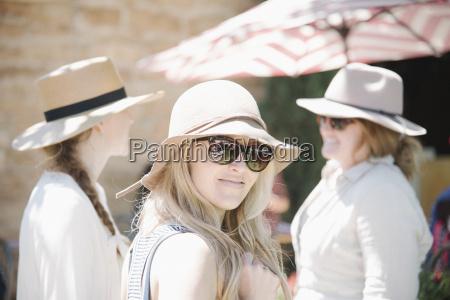 portrait of three women wearing hats