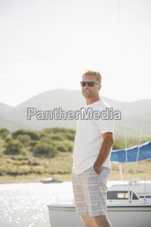 blond man wearing sunglasses standing on