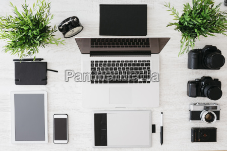desk of photographer with laptop cameras