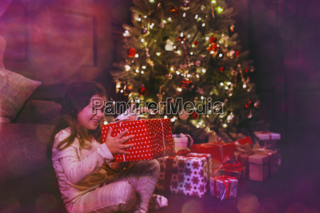 excited girl holding gift next to
