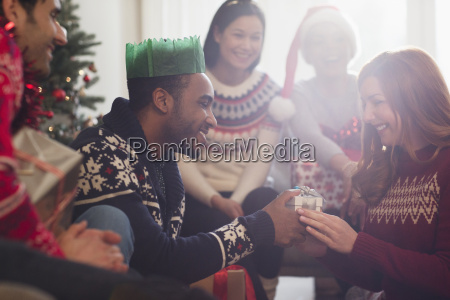 friends watching boyfriend giving christmas gift