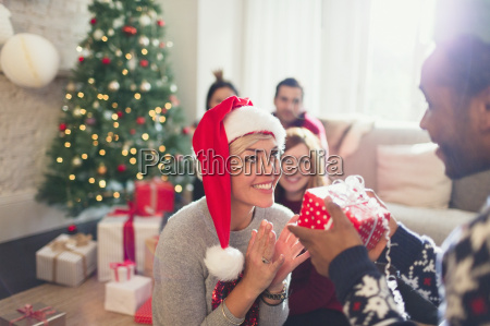 boyfriend giving excited girlfriend christmas gift
