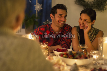 smiling couple enjoying candlelight christmas dinner
