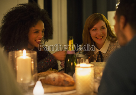 smiling friends drinking champagne at candlelight