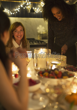 smiling friends enjoying candlelight christmas dessert