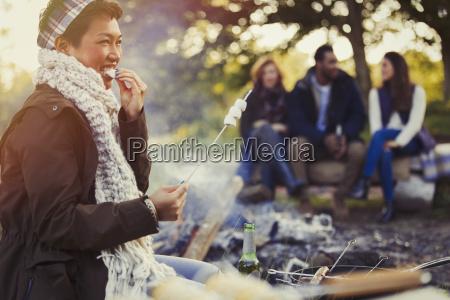 smiling woman eating roasted marshmallows at