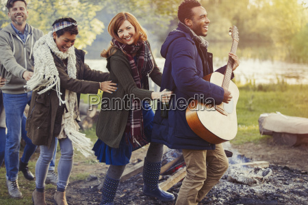 playful friends with guitar dancing in