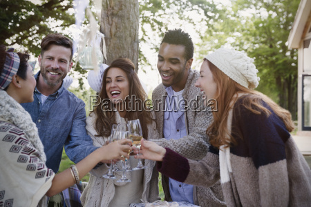 friends toasting champagne glasses on patio