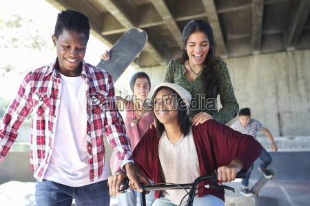 teenage friends with skateboards and bmx