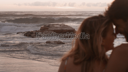 affectionate couple cuddling on ocean beach