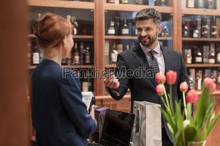 businessman paying clerk at liquor store