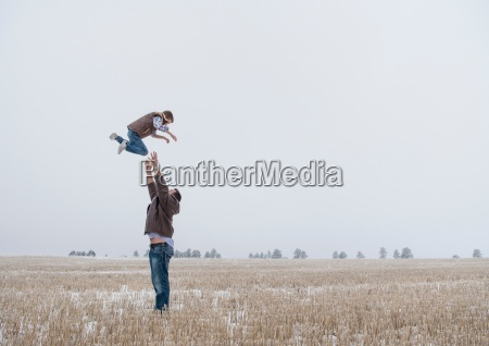 parent throwing child in air