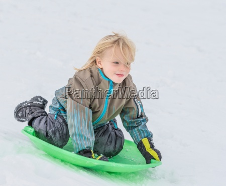boy playing on toboggan in snow