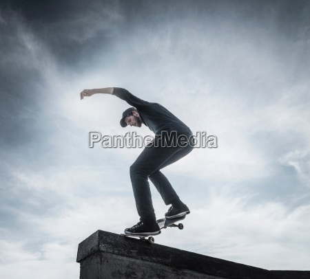 young man skateboarding on roof