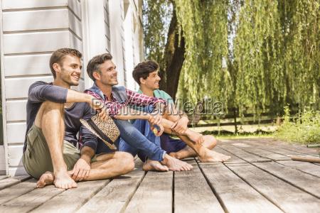 three men sitting on wooden decking
