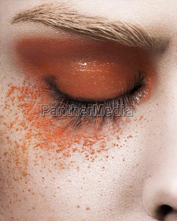 young woman with orange eye make