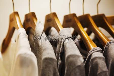 row of clothes on wooden hangers