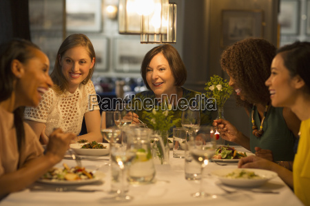 smiling women friends dining at restaurant