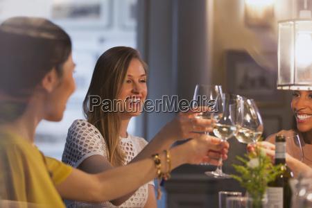 smiling women friends toasting white wine