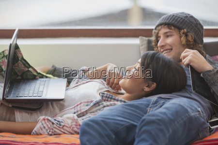 young couple relaxing laying using laptop