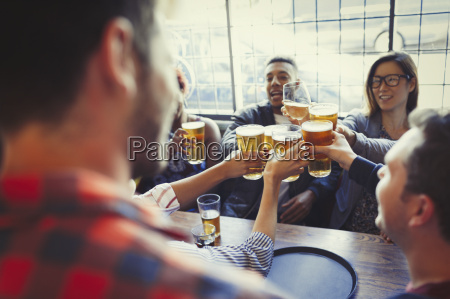 friends celebrating toasting beer glass at