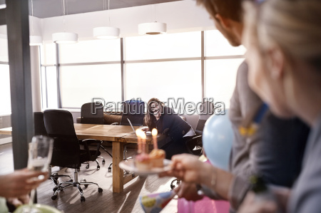 business people surprising businesswoman with birthday