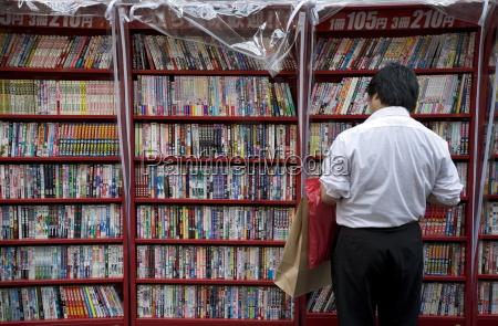 man browsing japanese manga comic books